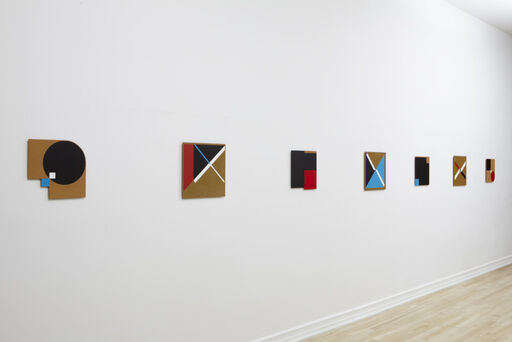 An installation view of seven small Tony Delap paintings, Mystic Myth, All Crossed Up, Mayne, Nothing to Hide, Galiano, Crossed Road, and Mysterious Feint.