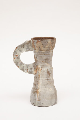 A grey, hourglass-shaped, abstract stoneware cup with a cylindrical, elongated base, and a large, flattened, handle and rim decorated with a zig zag pattern.