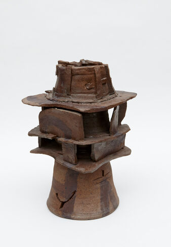 A large, primarily brown, abstract ceramic piece consisting of irregularly-shaped stoneware slabs and pieces, sandwiched between a cylindrical, stoneware jar.