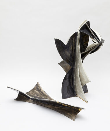 A large, abstract, geometric, fired ceramic in two parts, consisting of a standing jug composed of various white and black, curved pieces, and an angular, brown, white, and black dish.