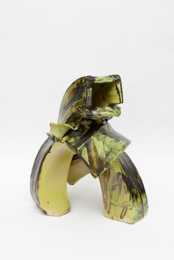A large, primarily green, yellow, and black abstract ceramic piece consisting of two standing, rectangular-shaped tubes, merging together at the center, with a hollow opening at the top.