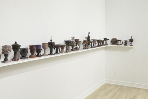 An installation view of half of Josh Smith's The Last Crusade, consisting of about twenty-two ceramic sculptures, of various sizes and colors, arranged on an L-shaped shelf.