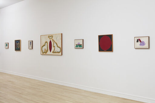 An installation view of four small, playful, colorful drawings by Joan Snyder, and three paintings by Forrest Bess. The Forrest Bess paintings consist of a black canvas with a large red circle, a painting featuring a roughly shaped unicorn, lion, and carbuncle outlined with gold paint, and a black canvas, consisting of a blue circle with four smaller blue spheres inside.