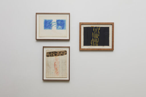 An installation view of a small Joan Snyder drawing of two blue boxes connected by lighter blue lines, a small Joan Snyder drawing of pink marks over a grid, collaged with a cheetah-patterned, horizontal strip, and a small, black Forrest Bess painting with vertical, yellow marks.