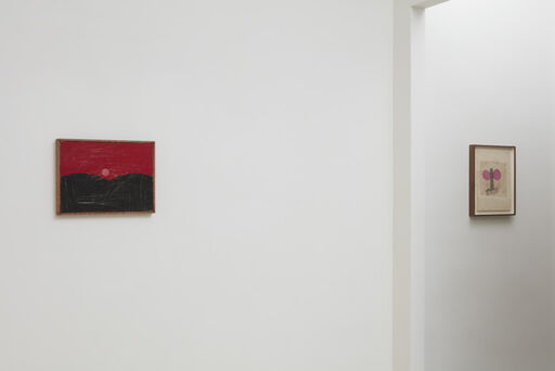 An installation view of a small, landscape painting by Forrest Bess, consisting of a black, hilly foreground and deep red horizon with an orange sun, and a small playful drawing by Joan Snyder, consisting of a blue strip bordered by two pink spheres.