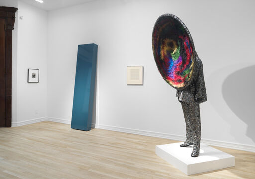 An installation view of a small black-and-white artwork by Robert Adams, a large, blue, leaning plank by John McCracken, a small work on paper by Agnes Martin, and a large, mixed-media sculpture by Nick Cave, of a suited man whose face is replaced by a massive, colorful, black hole-like circle.