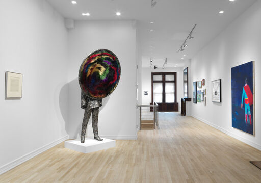 An installation view of a small work on paper by Agnes Martin, a large, mixed-media sculpture by Nick Cave, of a suited man whose face is replaced by a massive, colorful, black hole-like circle, and a large, blue painting of Superman by Katharine Bradford.