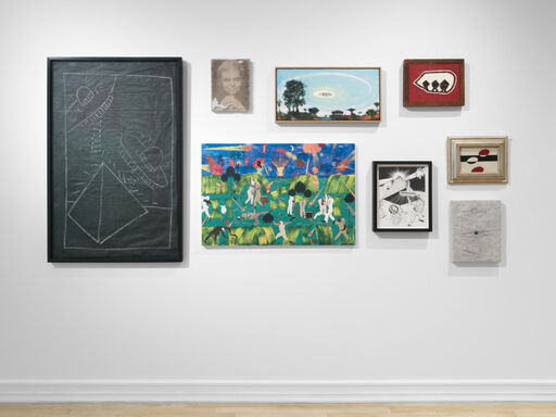An installation view consisting of a Keith Haring drawing of UFOs over a pyramid, a portrait by JPW3, a landscape by Verne Dawson, a red, white, and black abstract painting by Forrest Bess, an abstract painting of UFOs by Charles Shaw, a black-and-white, abstract work by Chris Churchill, a black-and-white drawing by Jim Shaw, and a saturated, cartoonish, landscape of an alien invasion by Andrea Heimer.