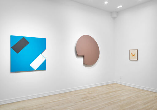 An installation view of a tan, monochrome, circular wall piece with a removed wedge, a drawing with sketchy orange and red lines, and a blue, hard-edged wall-piece with a black rectangle and white rectangle placed at angles in the corner of the piece, with a removed, triangular wedge.