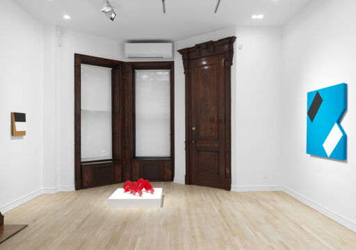 An installation view of a hard-edged, tan, rectangular wall piece with a black rhombus and a white rhombus, a red sculpture comprised of overlapping, looping triangles atop a low pedestal, and a blue, hard-edged wall-piece with a black rectangle and white rectangle placed at angles, with a removed, triangular wedge.