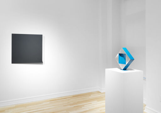 An installation view of a black, monochrome wall piece shaped like an asymmetrical square, and a diamond-shaped sculpture atop a pedestal, balancing on its point. The sculpture is silver with blue edges, and has a blue, square cavity in its center.
