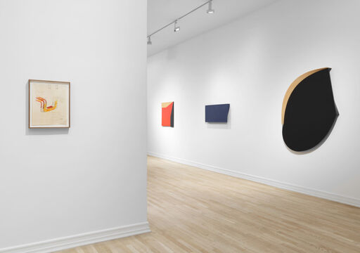 An installation view of a drawing with sketchy orange and red lines, a hard-edged, primarily black oval wall piece with a tan semi-circle and straight edge, a blue, asymmetrical, rectangular wall piece, and a hard-edged red, tan, and black wall piece.