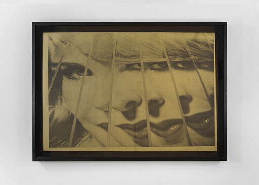 A sepia image of a smirking, blonde woman, fractured and contorted by seven diagonal lines.