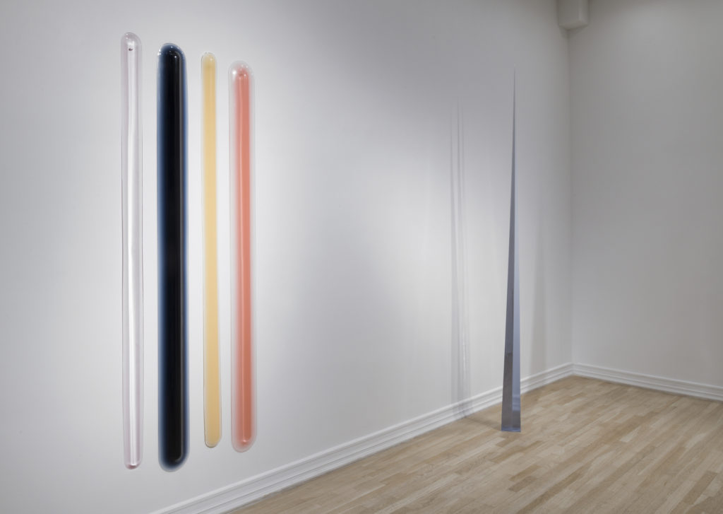 An installation view of two urethane sculptures, including a series of four large, vertical bars arranged in a horizontal row against the wall, rendered in translucent white, blue, yellow and peach, and a free-standing, vertical, needle-like sculpture rendered in translucent blue-grey.