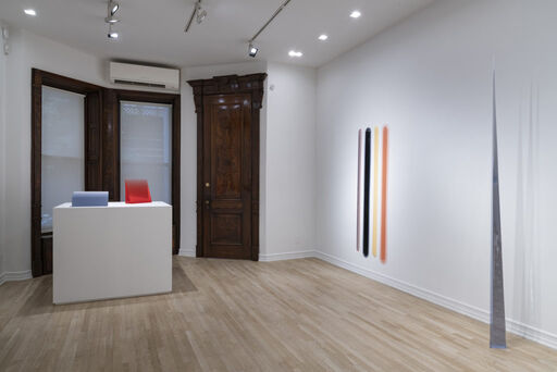 An installation view of five urethane sculptures, including a blue-grey wedge-like form, a translucent red, vertical wedge-like form, a free-standing, blue-grey needle-like form, and a series of four large white, blue, yellow, and peach vertical bars.