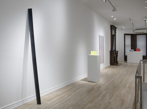 An installation view of an inky-black, leaning, urethane column sculpture, a translucent yellow, cube-like urethane sculpture atop a pedestal, a series of vertical urethane bars arranged in a horizontal row, and two wedge-like urethane sculptures rendered in light blue and red.