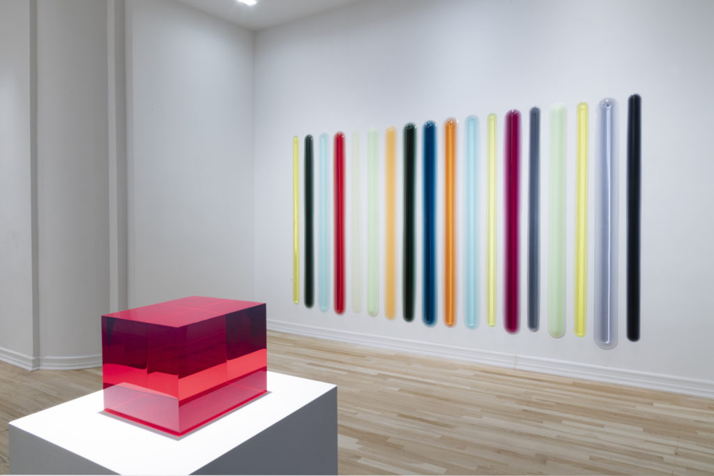 An installation view of a translucent, red, cube-like urethane sculpture atop a pedestal, and a series of eighteen large, vertical urethane bars arranged in a horizontal row. The bars are cast in an array of translucent, vibrant colors including magenta, yellow, orange, red, and teal.