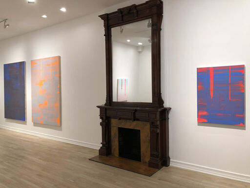 An installation view consisting of a large, primarily black abstract painting revealing cobalt layers and brushstrokes, a large, primarily grey abstract painting revealing orange layers and brushstrokes, and a medium-sized, cobalt-blue canvas revealing bright red layers and brushstrokes.