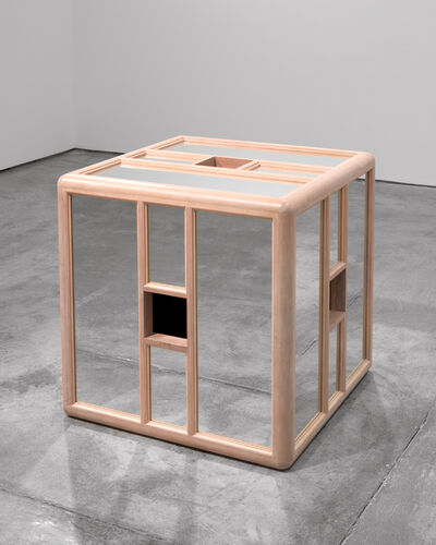 A sculpture shaped like a cube, surrounded by segments of reflective glass and light-colored wood.