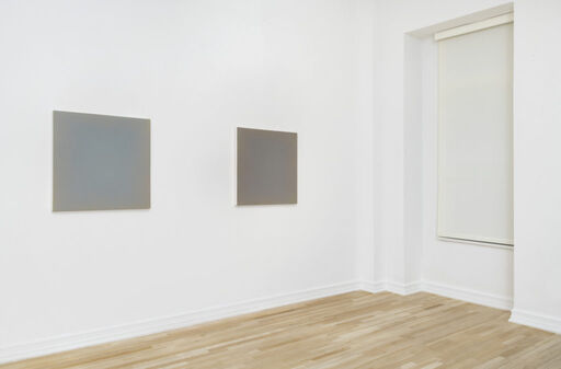 An installation view of Anne Appleby's Last Light (August), a primarily blue-grey monochrome square, and Last Light (After the Rain), a primarily purple-grey monochrome square.