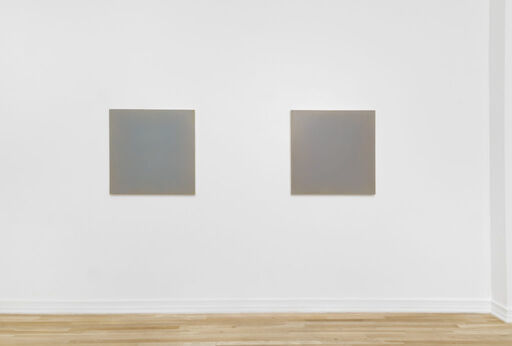 A head-on installation view of Anne Appleby's Last Light (August), a primarily blue-grey monochrome square, and Last Light (After the Rain), a primarily purple-grey monochrome square.