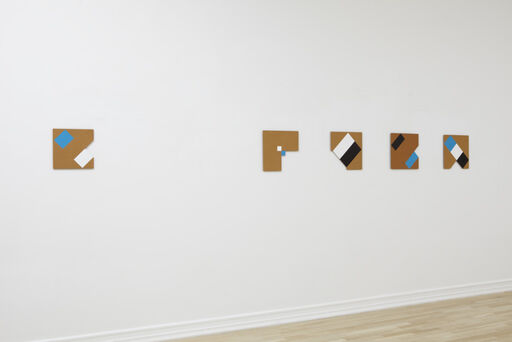An installation view of five small Tony Delap paintings, Vortex, RuVuBu, What the Hell?, The Inseparable Pair, and New Today.