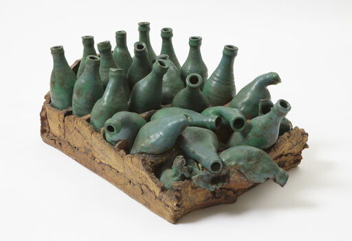 A glazed ceramic piece consisting of a textured, brown crate with about twenty green, bending bottles, falling and melting upon one another.