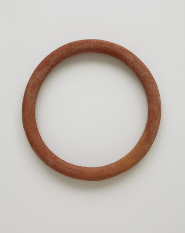 An orange-red circular disk with a hollow center, crafted from brick and brick dust.