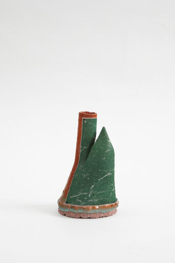 A small, abstract, cast earthenware piece consisting of a primarily green form, segmented at the top to form a sharp point and a green and orange, hollow tube. The rounded base of the piece consists of a pink, turquoise, and orange stripe.