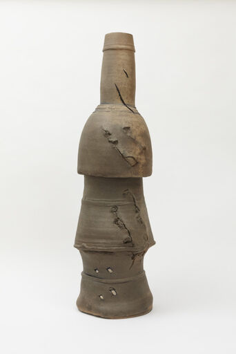 A large, abstract, brown, stoneware and porcelain pot consisting of a tiered stack of three bell-shaped components, with a hollow cylinder emanating from the top. The surface of the piece is scratched and punctured.