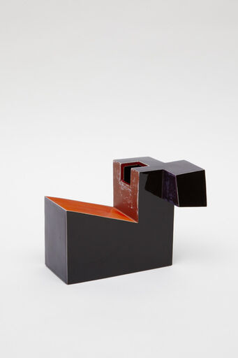 An abstract glazed ceramic piece, consisting of a black, geometric form with a hollow, cube-like indentation and angular, cube-like appendage. The slanted surface, and vertical edge at the top of the piece is painted red.