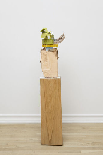 An abstract, mixed media piece consisting of a large peach-colored block, positioned vertically atop a wooden pedestal. The block is stacked with a variety of small green, yellow, and blue angular forms and decorated with fluid, organic, purple-grey forms.