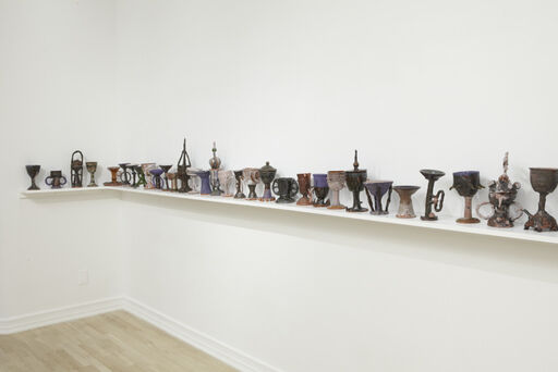 An installation view of half of Josh Smith's The Last Crusade, consisting of about twenty-three ceramic sculptures, of various sizes and colors, arranged on an L-shaped shelf.