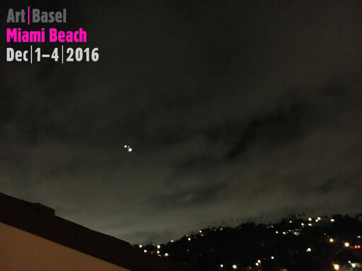 This image displays the Art Basel Miami Beach logo text, written upon an image of an urban landscape at night.