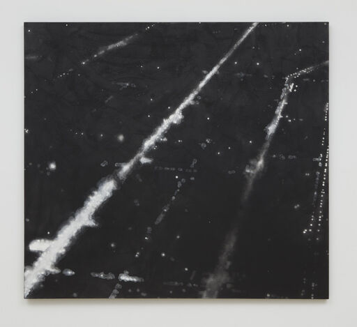 A primarily black aerial landscape, consisting of a series of white, long, diagonal lines, and smudged white dots resembling street lights. The composition is reminiscent of the view outside a plane window at night.