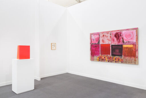 An installation view consisting of an orange-red, vertical, urethane rectangle by Peter Alexander, an abstract painting by Joan Snyder consisting of eight red, pink, orange, and white dripping rectangles arranged in a grid, and a small, indiscernible work on paper.