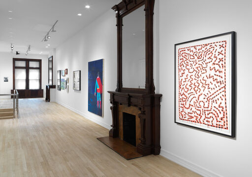 An installation view of a large Kieth Haring artwork of two playful, orange figures composed of orange lines with blue dots against a white background decorated with orange zig zags, and a large, blue painting of Superman by Katharine Bradford.