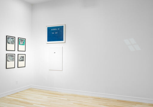 An installation view of four green, black, and white works on paper by Mike Kelley arranged in a grid, a blue artwork by Ed Ruscha with white text, and a primarily white canvas with an indiscernible, black mark in the top center.