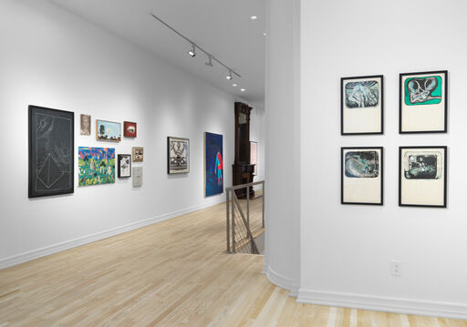 An installation view of four green, black, and white works on paper by Mike Kelley arranged in a grid. In the background of the image, nine artworks are displayed in a tight, small-scale grouping, adjacent to two larger works.