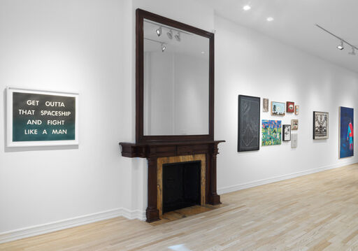 """An installation view of a blue-grey, pastel Ed Ruscha drawing with white text that reads, """"GET OUTTA THAT SPACESHIP AND FIGHT LIKE A MAN."""" In the background of the image, nine artworks are displayed in a tight, small-scale grouping, adjacent to two larger works."""