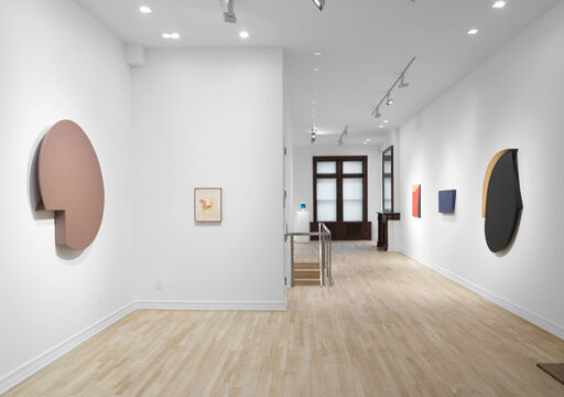 An installation view of a tan, monochrome, circular wall piece with a removed wedge, a drawing with sketchy orange and red lines, a hard-edged, primarily black oval wall piece with a tan semi-circle and straight edge, a blue, asymmetrical, rectangular wall piece, and a hard-edged red, tan, and black wall piece.