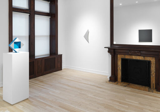 An installation view of a silver, monochrome wall piece, shaped like a triangle with a curved edge, and a diamond-shaped sculpture atop a pedestal, balancing on its point. The sculpture is silver with blue edges, and has a blue, square cavity in its center.