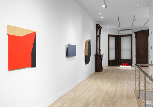 An installation view of an irregularly-shaped, hard-edged red, tan, and black wall piece, a blue, protruding, asymmetrical, rectangular wall piece, a hard-edged, primarily black oval wall piece with a tan semi-circle and straight edge, and an indiscernible red sculpture atop a low pedestal.