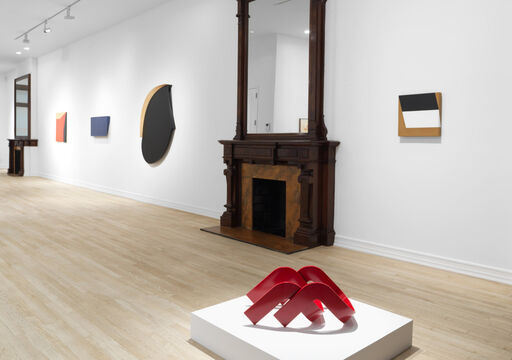 An installation view of a red sculpture comprised of overlapping triangles atop a low pedestal, a hard-edged, tan, rectangular wall piece with a black rhombus and a white rhombus, a hard-edged, primarily black oval wall piece with a tan semi-circle and straight edge, a blue, asymmetrical, rectangular wall piece, and a hard-edged red, tan, and black wall-piece.
