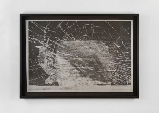 A black-and-white image of a shattered window. The fractured glass creates a dense, weblike pattern on the window's surface, that emanates from its center.