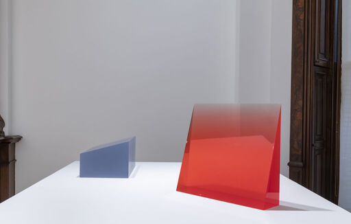 An installation view of two urethane sculptures atop a pedestal, including a semi-translucent, blue-grey, horizontal wedge-like form, and a translucent, bright red, vertical wedge-like form.