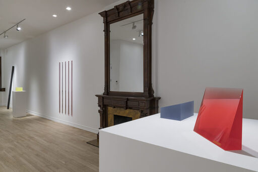 An installation view of five urethane sculptures, including a blue-grey wedge-like form, a translucent red, vertical wedge-like form, a series of five lustre pink and white vertical bars, an inky-black, leaning column sculpture, and a translucent yellow, cube-like sculpture.