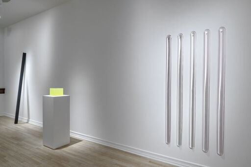 An installation view of an inky-black, leaning, urethane column sculpture, a translucent yellow, cube-like urethane sculpture atop a pedestal, and a series of five vertical urethane bars arranged in a horizontal row, cast in lustre pink and white pearl-like colors.