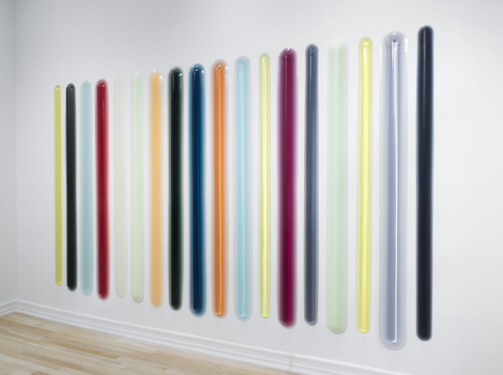 A sculpture consisting of eighteen large, vertical urethane bars arranged in a horizontal row against the wall, and cast in an array of translucent, vibrant colors including magenta, yellow, orange, red, and teal.