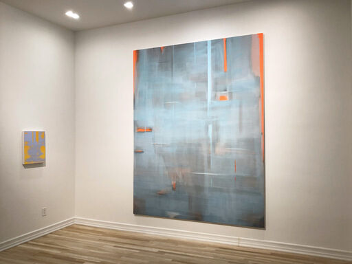 An installation view consisting of a lavender and mustard yellow small, abstract painting, and a large, primarily light blue, abstract painting with orange vertical and horizontal lines at its edges.